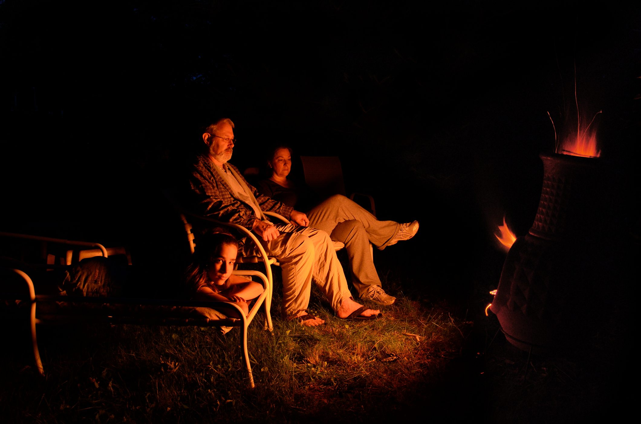 Photograph of Lanie, Gary and Ginger Allman sitting in the backyard lit by the orange glow of a chiminea