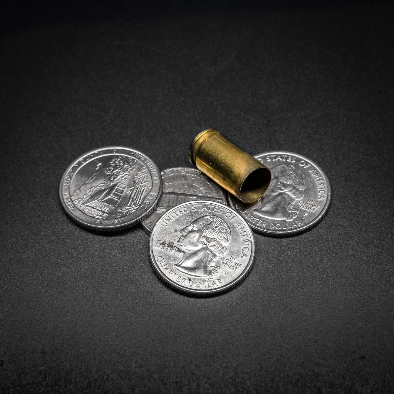 Photograph showing three quarter coins and a spent 9mm round casing