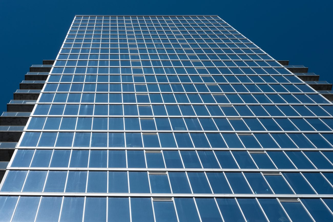 Office building with blue windows and a blue sky. E 13th. Kansas City