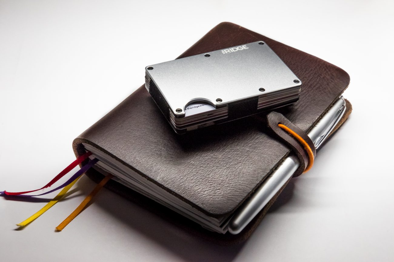 Photograph of an aluminium The Ridge Wallet on a leather journal