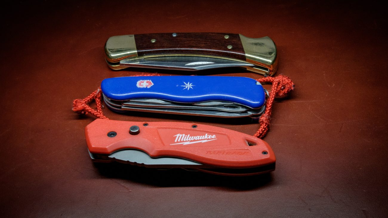 Photograph of a Buck 110 Knife, A Swiss Navy Knife and a Milwaukee Fastback Knife