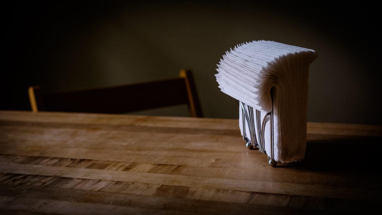 Color photograph of paper napkins in a holder on a wooden kitchen table