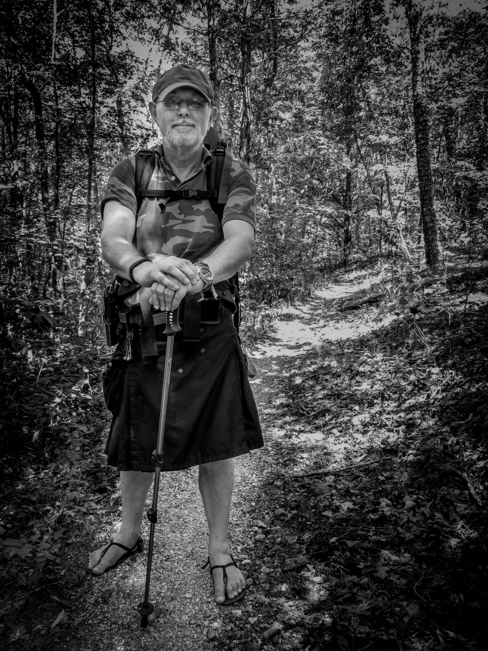 Black and White photograph of Gary Allman backpacking on the Ozark / Berryman Trail. Gary is wearing a kilt and huaraches.