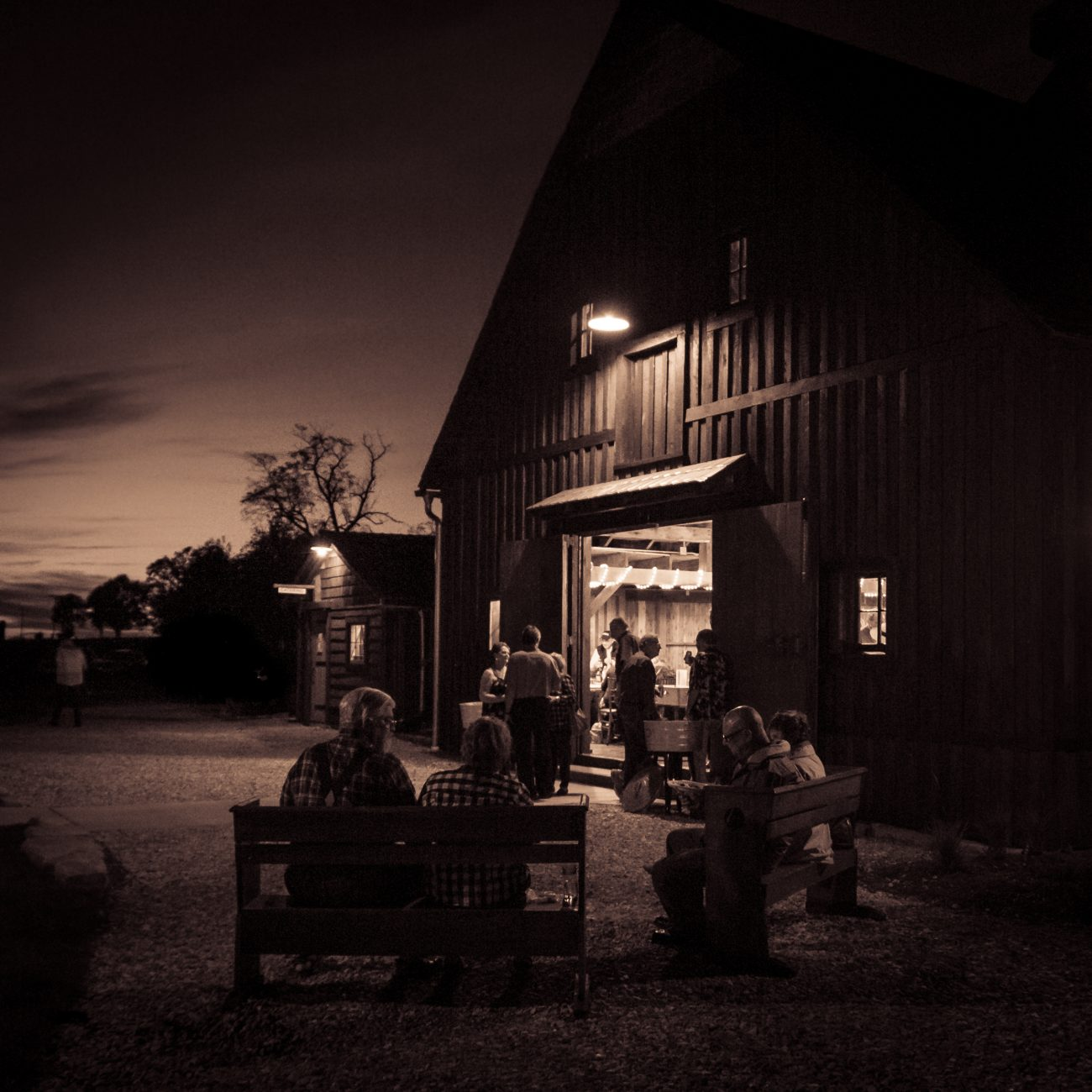 Duotoned photograph of people sitting and standing outside a barn eating and conversing in the twilight